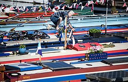 © Licensed to London News Pictures. 05/05/2018. London, UK. A boat owner adjusts bunting on his boat as the Canalway Cavalcade festival takes place in Little Venice, West London on Saturday,  May 5th 2018. Inland Waterways Association's annual gathering of canal boats brings around 130 decorated boats together in Little Venice's canals on May bank holiday weekend. Photo credit: Ben Cawthra/LNP