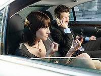 Couple at back seat of car woman applying make-up man using mobile phone