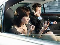 Couple at back seat of car woman applying make-up man using mobile phone