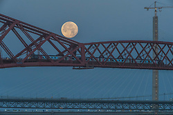 The setting Super-moon behind the Forth Bridge near to Edinburgh