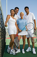 Four mixed doubles tennis players at net on tennis court low angle view