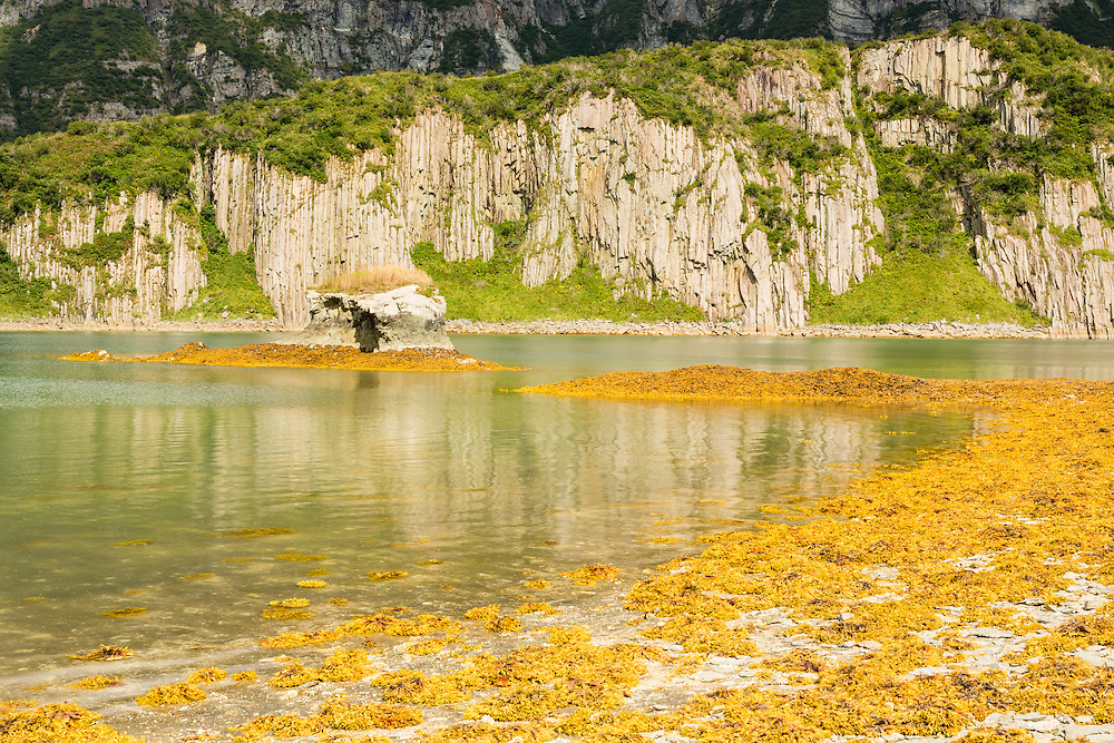 Basalt cliffs line the entrance of Geographic Harbor in Katmai National Park in Southwestern Alaska. Summer. Afternoon.