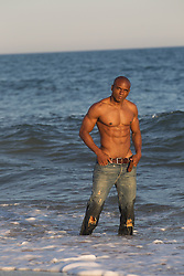 sexy shirtless man coming out of the ocean at sunset