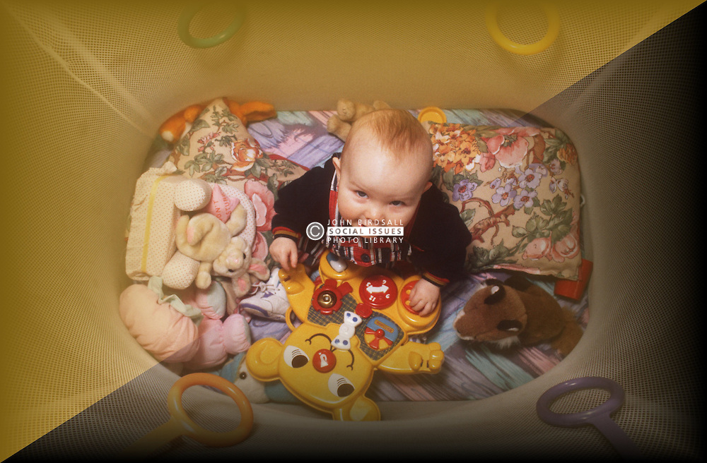Young baby sitting in playpen playing with toys,