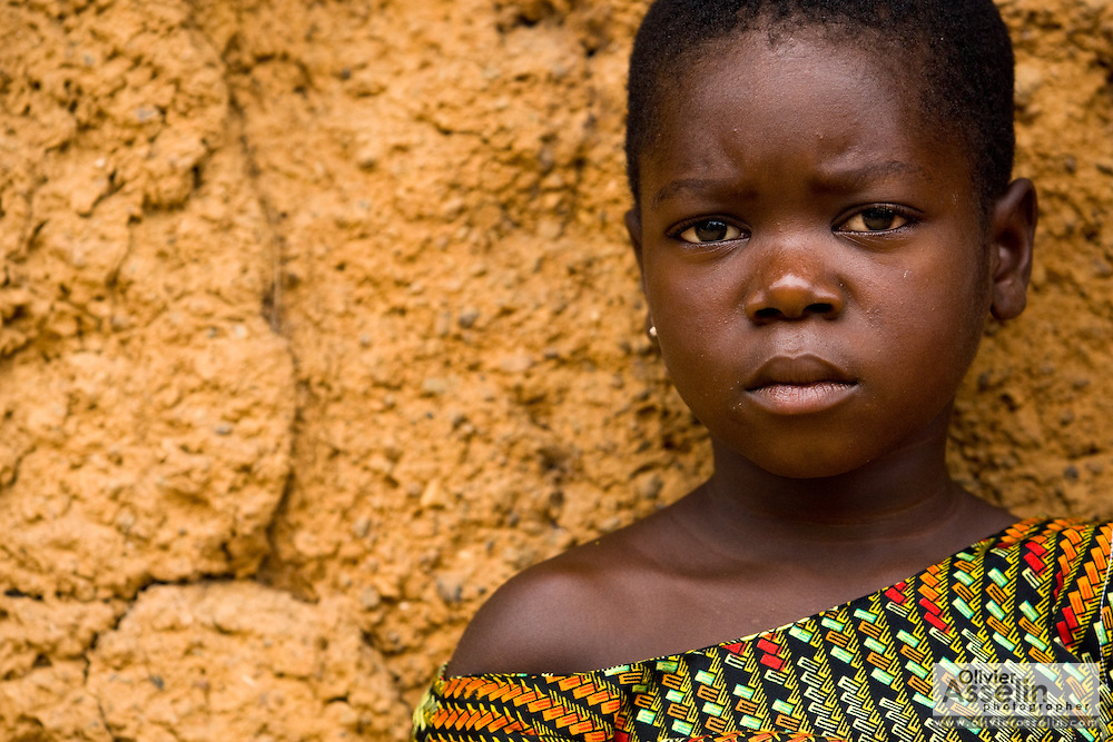 Mira Akissi leans against a mud hut in Tano Akakro, Cote d'Ivoire on Saturday June 20, 2009.