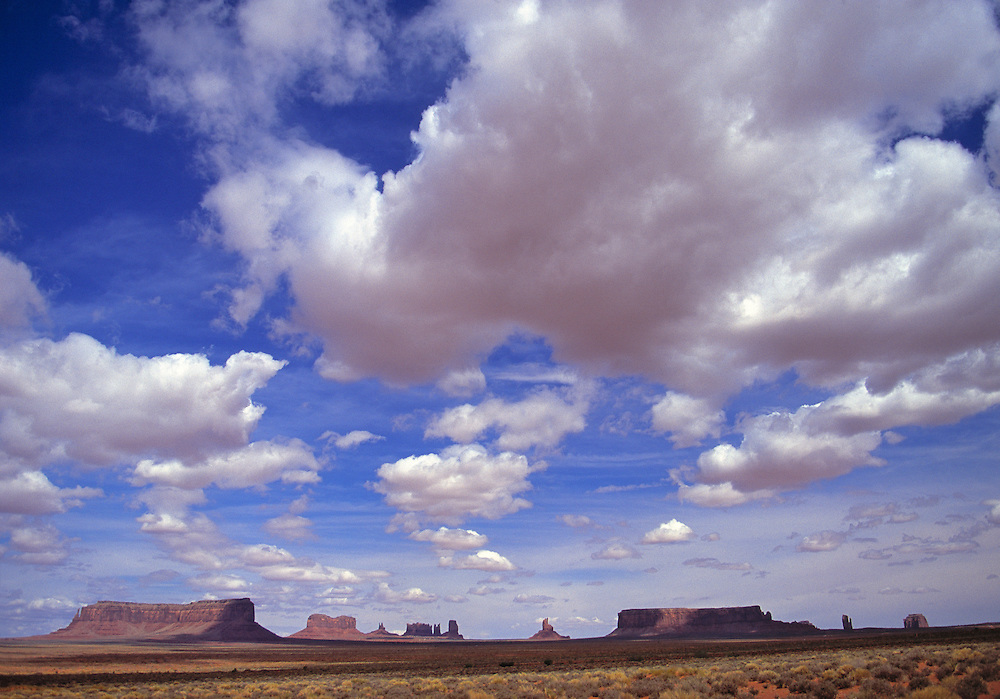 A cloud-filled summer sky floats over the buttes in Monument Valley, Utah.