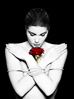 portrait studio of a woman smelling a rose chained by a neckless pearls