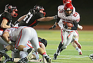 Iowa City High's Bryson Runge (28) pulls away from Linn-Mar's Steven Mercil (51) on a run during during the game between the Iowa City High Little Hawks and the Linn-Mar Lions at Linn-Mar Stadium in Marion on Friday October 12, 2012.