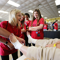 Allie Burrow, 14, from Guntown Middle School learns how to wrap an ankle at the Athletic Trainer booth during Thursday's Caeer Expo at the BancorpSouth Arena in Tupelo.