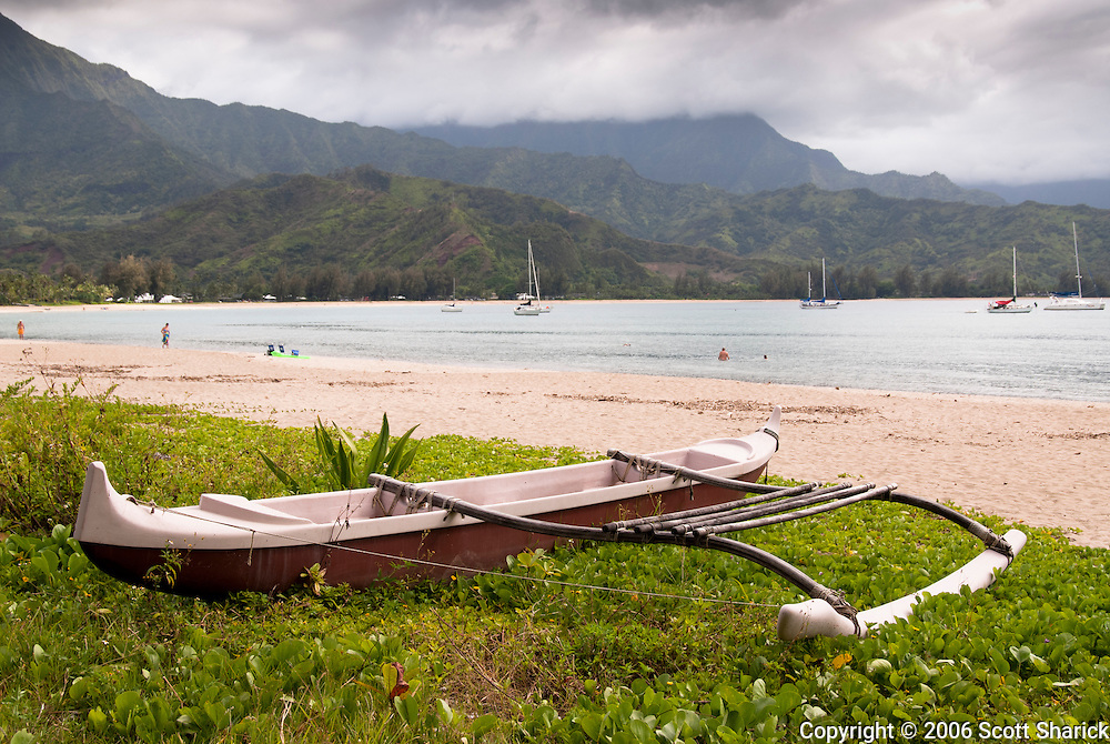 An outrigger canoe sits along the beach on Hanalei Bay, Kauai, Hawaii.