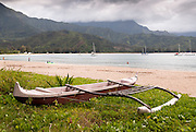 An outrigger canoe sits along the beach on Hanalei Bay, Kauai, Hawaii.