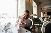 Smiling young businesswoman text messaging on cell phone at restaurant table