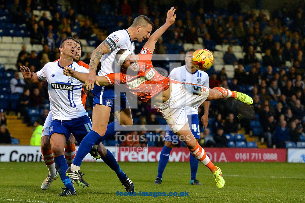 Peter Clarke of Bury (2nd left) heads clear under pressure from Tom Aldred of Blackpool during the Sky Bet League 1 match at Gigg Lane, Bury<br /> Picture by Ian Wadkins/Focus Images Ltd +44 7877 568959<br /> 31/10/2015