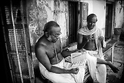 Two gentlemen in the morning. In a small housing area (village) which obviously is linked with the temple closeby. Chennai. Tamil Nadu State.