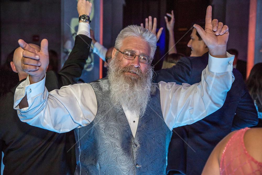 man with a beard celebrating at a wedding reception