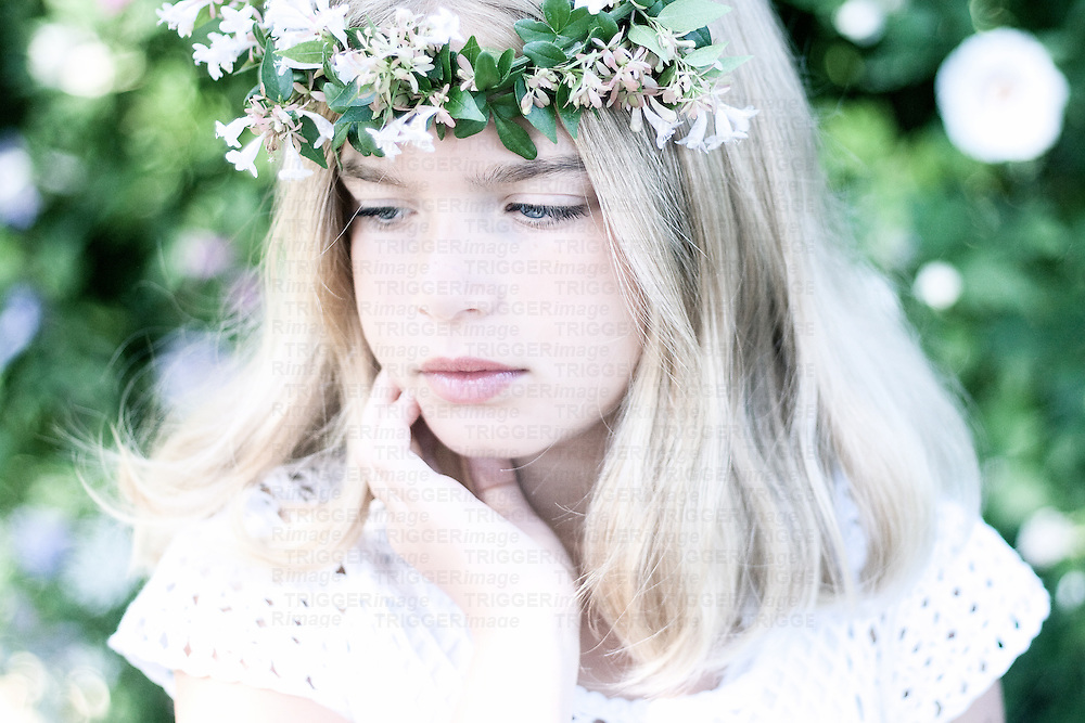 Close up of young child with blonde hair wearing floral garland looking down