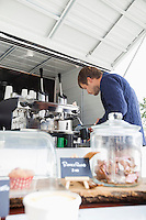 Young man preparing coffee at mobile shop