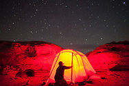 A man opens the entrance to his tent as stars shine overhead in the night sky just outside of Canyonlands National Park in Utah.