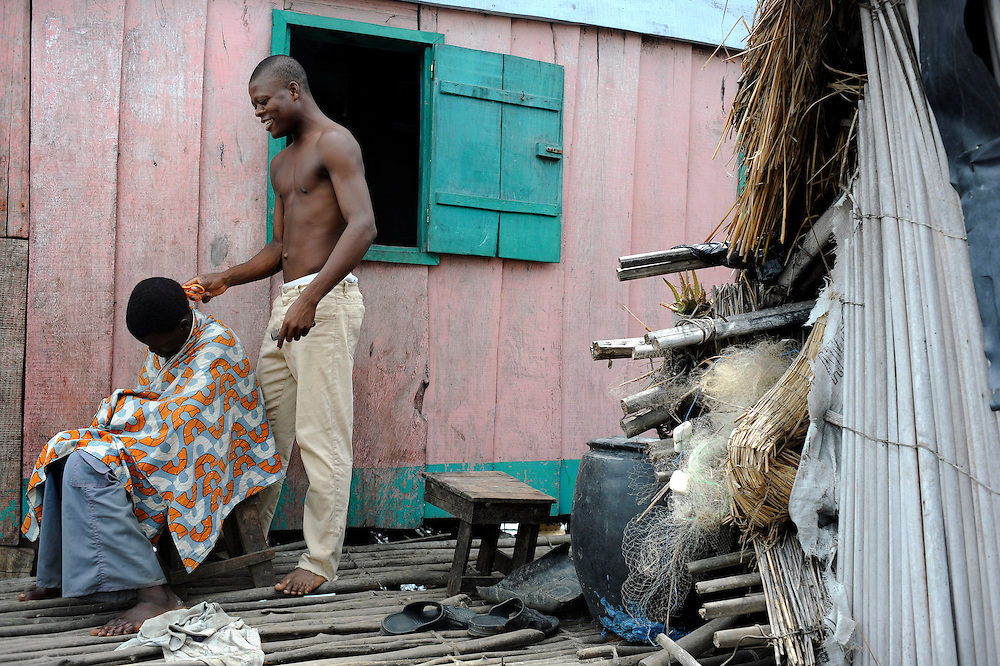 A barber prepares to cut a customer's hair with scissors and comb in hand in Cotonou, Benin on March 1, 2008.