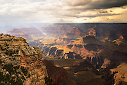 Afternoon sunlight shines through a light mist of rain filling the air in the Grand Canyon with a subtle glow.