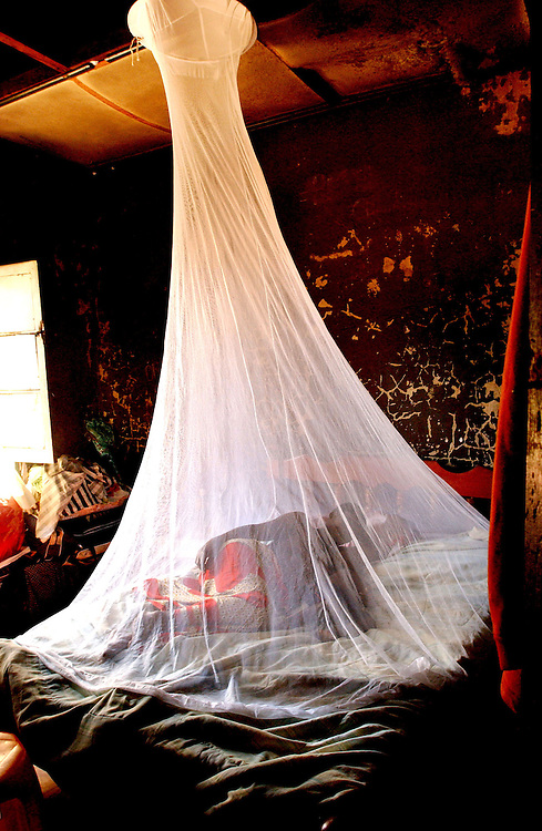 Isobel who is 9 months pregnant rests with one of her children under a mosquito net in her house in Luena, Angola..