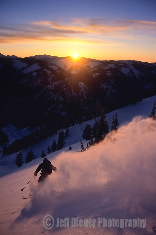 Powder snow billows into the air as a backountry skier makes turns on Teton Pass at sunset in Jackson Hole, Wyoming.