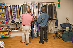 Men looking at clothes in a charity shop,