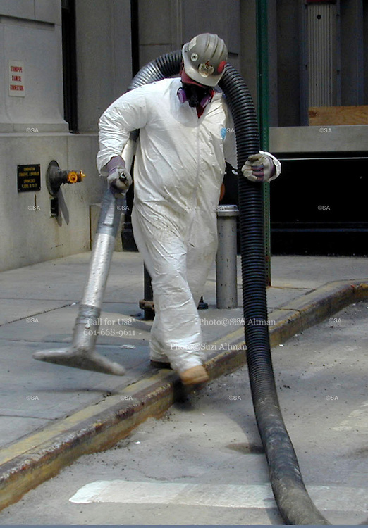 """Workers wear protective gear while cleaning the streets in lower Manhattan days after the Sept. 11th attack. Through my eyes and with my camera I am able to see the world we live in, and try to bring things into focus. Photography preserves my vision of what """"I see"""" at a specific time and place- a moment. Creating a bond between  me and my subject and capturing and emotion for eternity. Having lived and worked in New York City for over 15 years when 911 happened. I had to go and """"see"""" with my camera what lower Manhattan was like after this horrific attack on our Nation. The World Trade Center owned the skyline in lower Manhattan making it feel more like a canyon. After the Twin Towers fell, and I saw with my own eyes and camera the destruction, I realized what little land they actually sat on. The Twin Towers may not have occupied a large plot of land but they now touched everyones life. Photo©SuziAltman"""