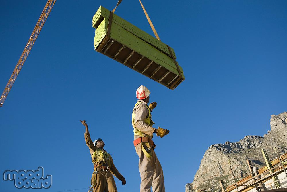 Workmen manoeuvre building materials on tower crane