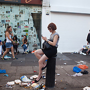 A woman stays clear of the rubbish in Portobello Road sitting on a post while she is on the phone. The Notting Hill Carnival has been running since 1966 and is every year attended by up to a million people. The carnival is a mix of amazing dance parades and street parties with a distinct Caribbean feel.