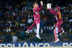 © Licensed to London News Pictures. 07/10/2012. West Indians Sunil Narine and Denesh Ramdin jump in celebration after getting a wicket during the World T20 Cricket Mens Final match between Sri Lanka Vs West Indies at the R Premadasa International Cricket Stadium, Colombo. Photo credit : Asanka Brendon Ratnayake/LNP