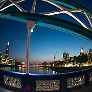 A view of the London skyline at dusk, with some of Tower Bridge in the foreground. In the far background to the left is The Shard, the tallest building in the European Union.