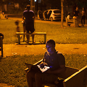 Cubans gather with their computer laptops or smart phones at night in WiFi hot spots, mostly in neighborhood parks where locals congregate to surf the internet, make face time calls or check their out FaceBook and email accounts. Photography by Jose More