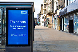 Edinburgh, Scotland, UK. 29 March, 2020. Life in Edinburgh on the first Sunday of the Coronavirus lockdown. Streets deserted, shops and restaurants closed, very little traffic on streets and reduced public transport. Pictured; Princes Street with NHS billboard at bus stop.. Iain Masterton/Alamy Live News