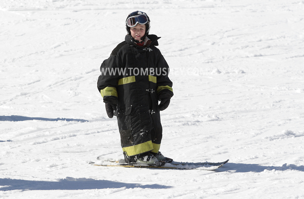 Bridgeville, New York - A young skier wearing a firefighter's coat awaits for the start of the firemen's races at Holiday Mountain on March 6, 2010.