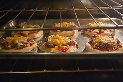 09 October 2014:   Small individual pizzas made from pillsbury biscuits, Italian meat sauce, mozzarella cheese, onion and ground beef broil in the oven to a bubbling hot morsel of enjoyment for those who are ready to consume