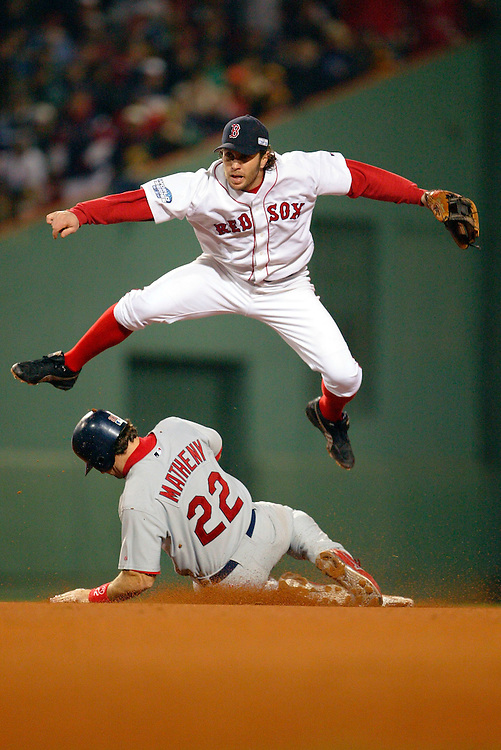 BOSTON- OCTOBER 24: Mark Bellhorn of the Boston Red Sox leaps over a sliding Mike Matheny of the St. Louis Cardinals during Game Two of the 2004 World Series at Fenway Park in Boston, Massachusetts. (Photo by Ron Vesely)