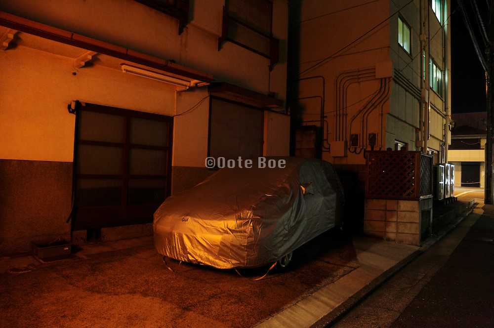 covered car parked in front of building during night