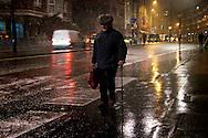 An elderly man walks through a snow flurry in Aldersgate Street, London EC1