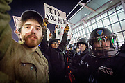 """Protesters and NYPD police officers in riot gear face off in a spontaneous protest outside Terminal 4 at the JFK Airport in New York. One protester holds a poster """"It's you next"""". The demonstrators partially shut down the terminal in protest of President Trump's immediate travel ban from seven predominately muslim countries."""