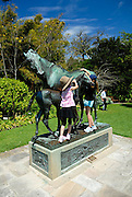 Children (10 years old, 6 years old) playing on bronze mare (La Reyna) and her foal by the French artist, Arthur J. le Duc. Royal Botanic Gardens, Sydney, Australia