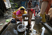 Shahnaz Hossain Begum rinses tiny fish for dinner at a village well in  Bari Majlish, an hour outside Dhaka, Bangladesh. (From the book What I Eat: Around the World in 80 Diets.)  The caloric value of her day's worth of food for a typical day in December was 2000 kcals. She is 38 years of age; 5 feet, 2 inches tall; and 130 pounds. Her micro-loan-financed small businesses have enabled her to build six rooms that she rents out, each for $8.65 (USD) a month. MODEL RELEASED.