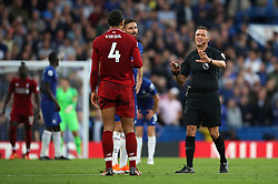 Match referee Andre Marriner mediates between Liverpool's Virgil van Dijk and Chelsea's Olivier Giroud during the Premier League match at Stamford Bridge, London.