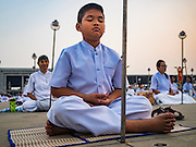 """22 FEBRUARY 2016 - KHLONG LUANG, PATHUM THANI, THAILAND: People pray during the Makha Bucha Day service at Wat Phra Dhammakaya.  Makha Bucha Day is a public holiday in Cambodia, Laos, Myanmar and Thailand. Many people go to the temple to perform merit-making activities on Makha Bucha Day, which marks four important events in Buddhism: 1,250 disciples came to see the Buddha without being summoned, all of them were Arhantas, Enlightened Ones, and all were ordained by the Buddha himself. The Buddha gave those Arhantas the principles of Buddhism, called """"The ovadhapatimokha"""". Those principles are:  1) To cease from all evil, 2) To do what is good, 3) To cleanse one's mind. The Buddha delivered an important sermon on that day which laid down the principles of the Buddhist teachings. In Thailand, this teaching has been dubbed the """"Heart of Buddhism."""" Wat Phra Dhammakaya is the center of the Dhammakaya Movement, a Buddhist sect founded in the 1970s and led by Phra Dhammachayo.      PHOTO BY JACK KURTZ"""