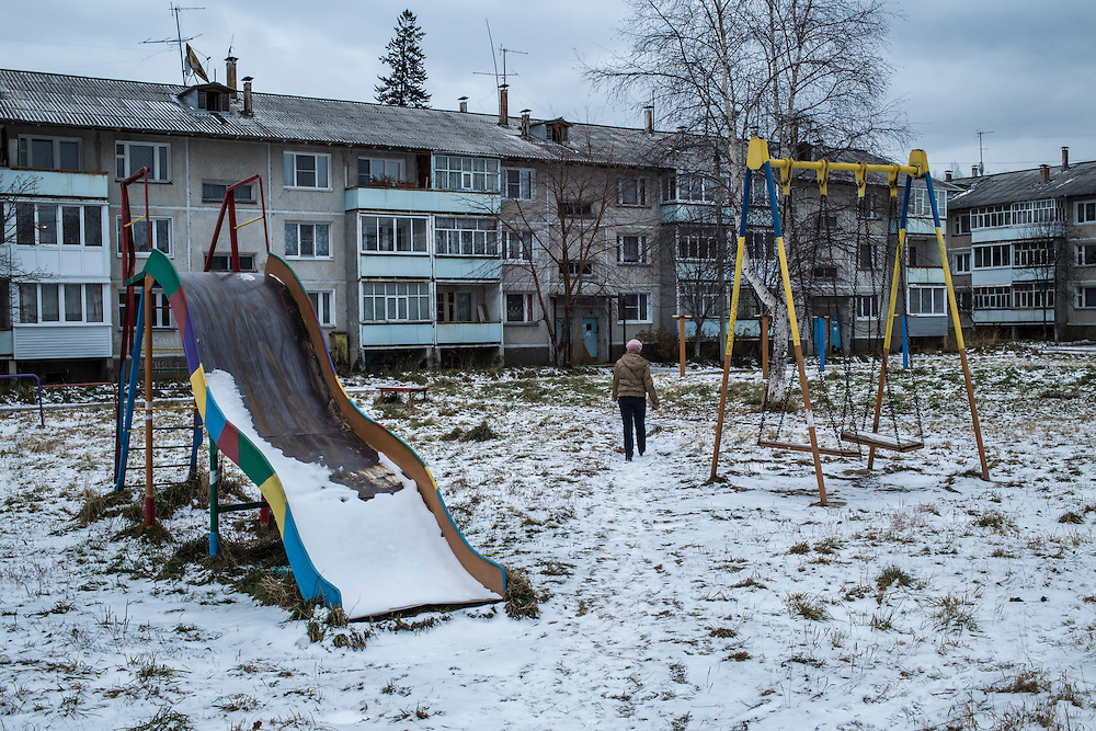 A woman walks through a playground outside a block of flats on Monday, October 21, 2013 in Baikalsk, Russia.