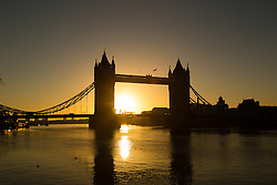 © Licensed to London News Pictures. 29/12/2013. London, UK. The sun rises behind Tower Bridge in London on a clear winter morning. Weather forecasts predict a dry and bright Sunday before more strong wind and heavy rain moves in early next week. Photo credit : Vickie Flores/LNP
