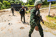 11 JULY 2013 - RAMAN, YALA, THAILAND: Thai soldies walk away from the scene of an IED attack against members of his unit Thursday. Eight soldiers were injured when the IED exploded under a Thai Army truck carrying soldiers back to their camp after they finished a teacher protection mision. The army routinely dispatches soldiers to protect teachers and Buddhist monks, who have been targeted by Muslim insurgents as representatives of the Bangkok government. More than 5,000 people have been killed and over 9,000 hurt in more than 11,000 incidents in Thailand's three southernmost provinces and four districts of Songkhla since the insurgent violence erupted in January 2004, according to Deep South Watch, an independent research organization that monitors violence in Thailand's deep south region that borders Malaysia.    PHOTO BY JACK KURTZ
