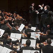"""December 12, 2012 - New York, NY : Conductor Gustavo Dudamel, standing at center, leads the  Westminster Symphonic Choir (not visible) and the Simón Bolívar Symphony Orchestra of Venezuela, along with tenor Idwer Álvarez, standing at right, and baritone Gaspar Colón, standing at left, as they perform Antonio Estévez's """"Cantata criolla"""" at Carnegie Hall's Stern Auditorium / Perelman Stage on Tuesday evening.  CREDIT: Karsten Moran for The New York Times"""