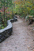 A dirt path with a rock wall follows Cedar Creek in Natural Bridge in Virginia.