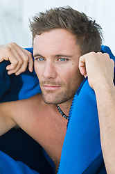Portait of a guy with blue eyes with facial stubble holding a blanket close to his head
